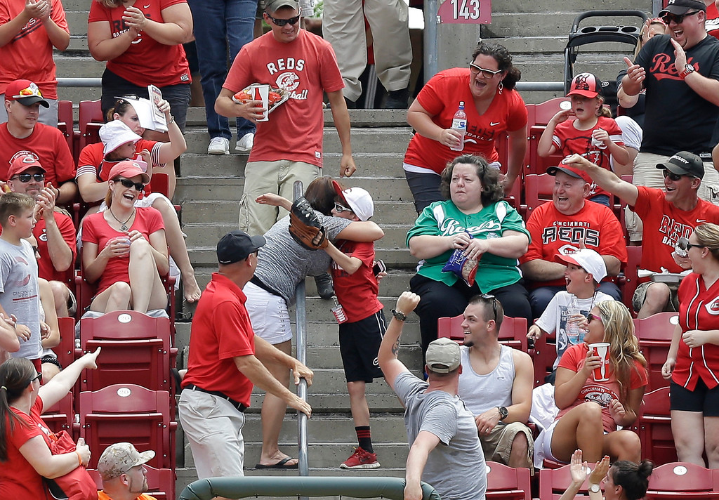 . A young fan gets a hug after catching a home run ball hit by Colorado Rockies\' Charlie Blackmon off Cincinnati Reds starting pitcher Homer Bailey in the fourth inning of a baseball game, Sunday, May 11, 2014, in Cincinnati. (AP Photo/Al Behrman)