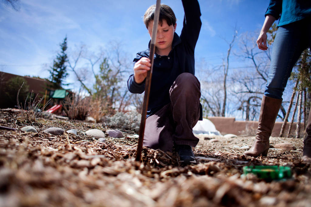 . Liam Downey, 10, pulls a measuring stick from an underground cistern in his parents\' Santa Fe home. A series of five connected 2,000-gallon tanks stores rain water and snow melt, which runs off the roof of the family\'s home. The water is then used to irrigate trees, shrubs and garden areas in the yard. (Special to the Pioneer Press: Mark Holm)