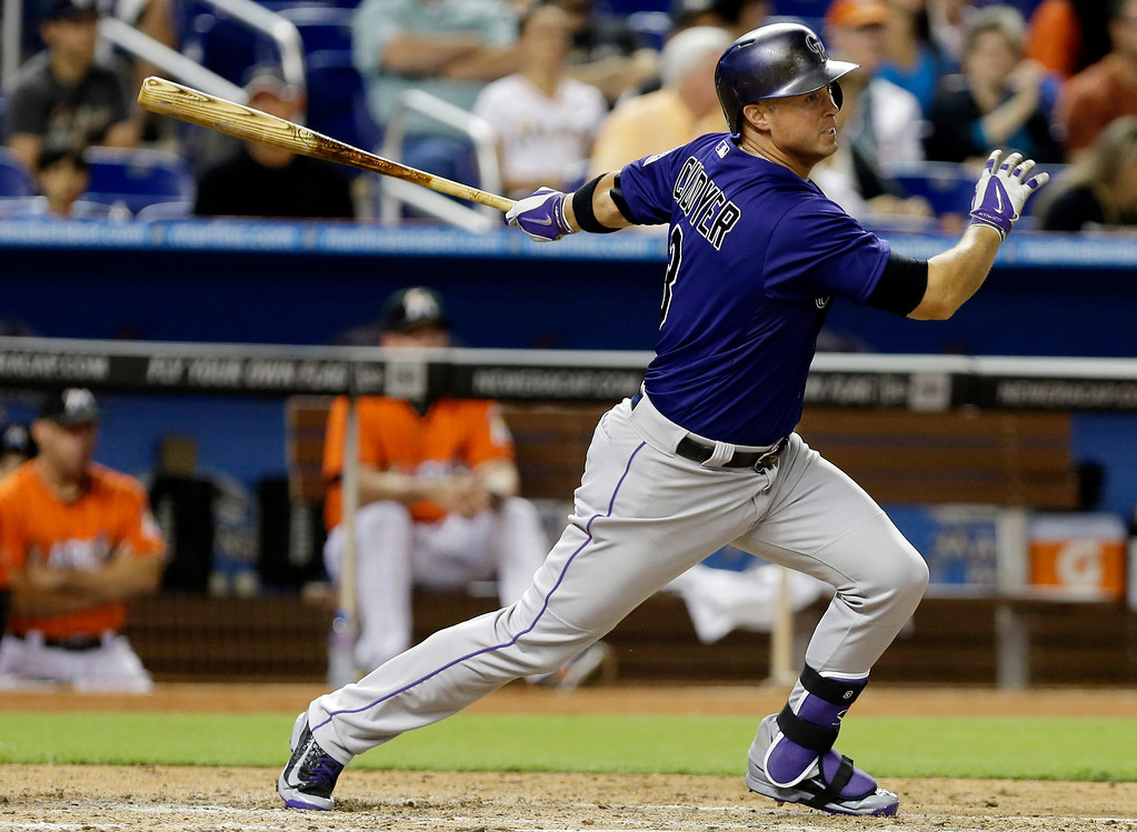 . Colorado Rockies\' Michael Cuddyer hits a single in the eighth inning of an opening day baseball game against the Colorado Rockies, Monday, March 31, 2014, in Miami. The Marlins defeated the Rockies 10-1.  (AP Photo/Lynne Sladky)