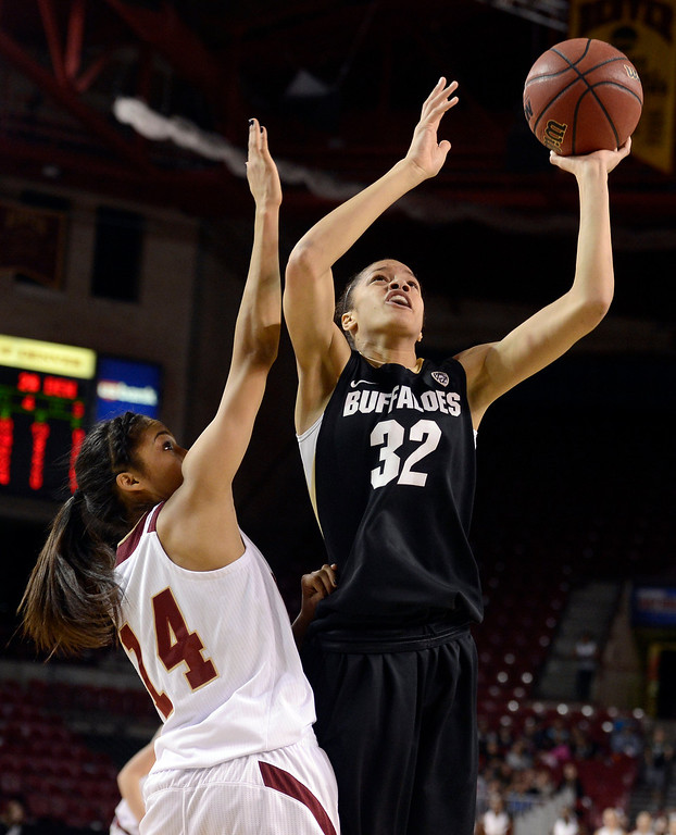 . University of Colorado\'s Arielle Roberson takes a shot over Kailey Edwards during a games against the University of Denver on Tuesday, Dec. 11, at the Magnus Arena on the DU campus in Denver.   (Jeremy Papasso/Daily Camera)