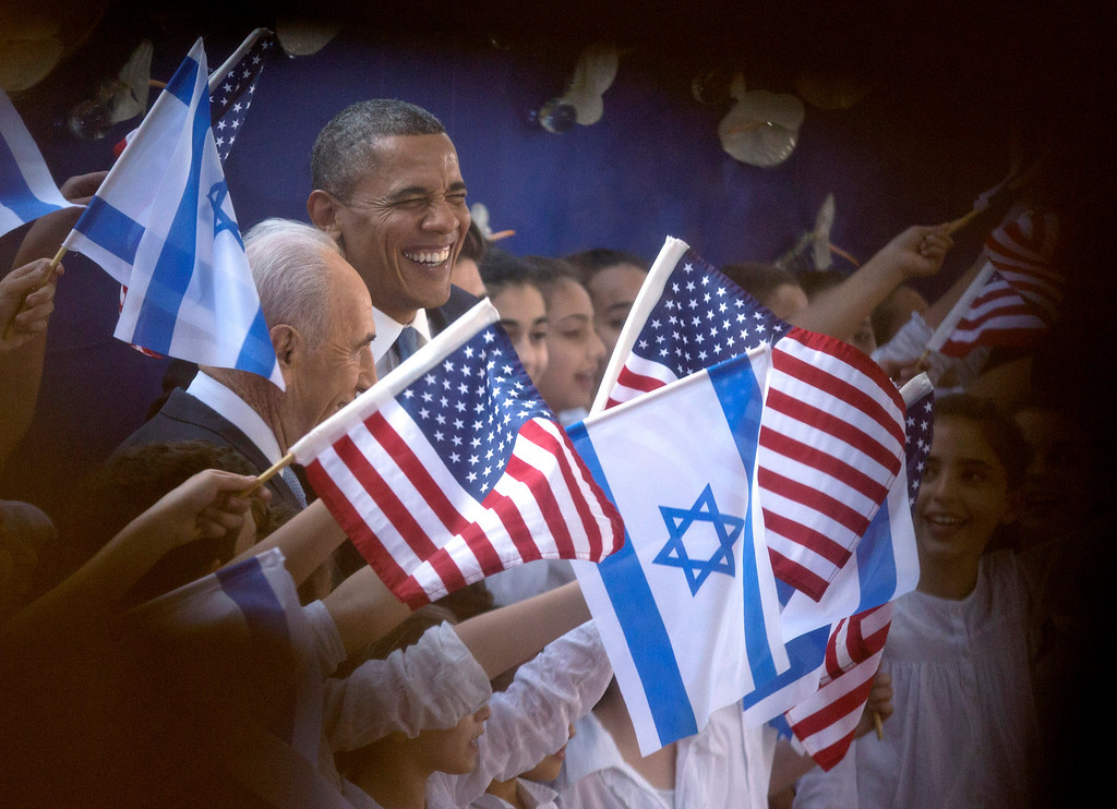 . President Barack Obama and Israeli President Shimon Peres, left, are photographed through a window and the crowd as they are greeted by children waving Israeli and American flags upon their arrival at the Peres\' residence, Wednesday, March 20, 2013, in Jerusalem. (AP Photo/Carolyn Kaster)