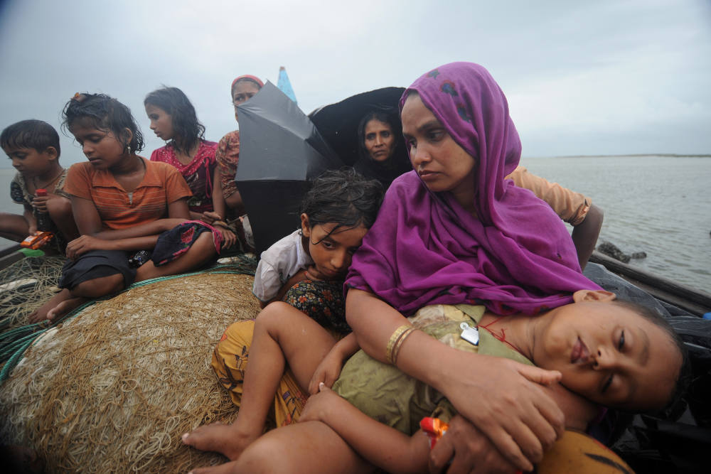 Description of . Rohingya Muslims, trying to cross the Naf river into Bangladesh to escape sectarian violence in Myanmar, look on from an intercepted boat in Teknaf on June 13, 2012. Bangladesh on Wednesday refused three more boatloads of Rohingya Muslims fleeing sectarian violence in Myanmar, officials said, despite growing calls for the border to be opened. Bangladeshi guards have turned back 16 boats carrying more than 660 Rohingya people, most of them women and children, since June 11 as they tried to enter from neighboring Myanmar across the river Naf. AFP PHOTO/ Munir  UZ ZAMAN/AFP/Getty Images
