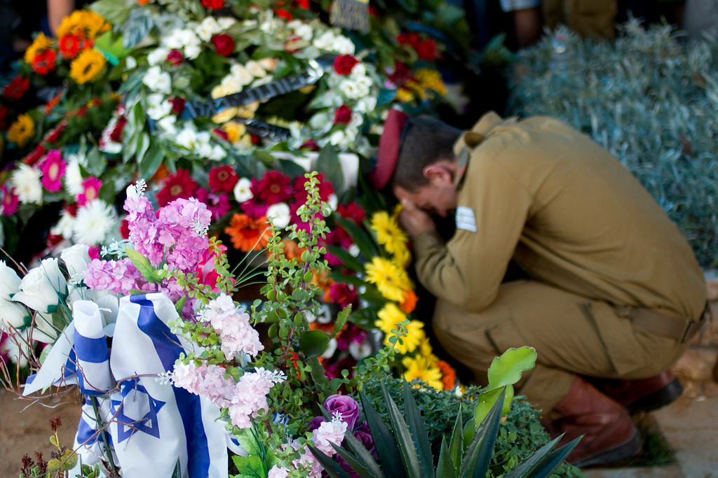 . An Israeli soldier of the Maglan elite unit morns over the grave of Staff Sgt. Matan Gotlib, a Maglan elite unit soldier, during his funeral in the military cemetery in Rishon Letzion, central Israel, Thursday, July 31, 2014. Gotlib, 21, was killed in combat on Wednesday in the southern Gaza Strip. (AP Photo/Ariel Schalit)