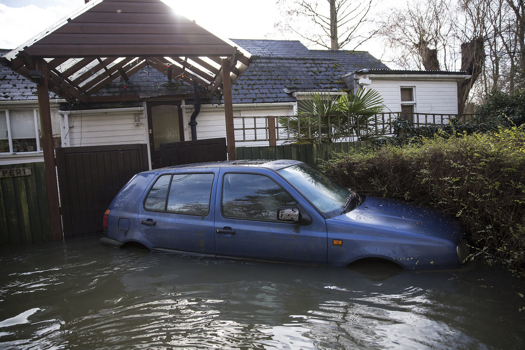 . A car stands partially submerged on a flooded road near the River Thames on February 13, 2014 in Wargrave, England.The Environment Agency continues to issue severe flood warnings for a number of areas on the River Thames in the commuter belt west of London. With heavier rains forecast, people are preparing for the water levels to rise. (Photo by Oli Scarff/Getty Images)