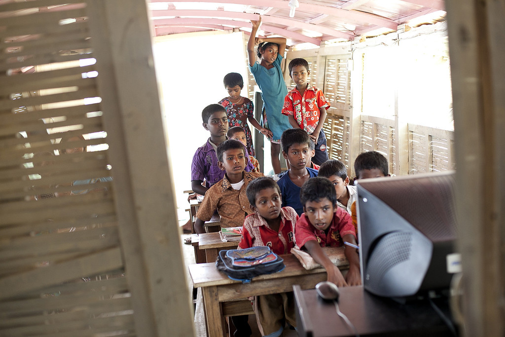 """. Children watch a cartoon on a computer in a solar powered \""""floating school\"""" operated by Shidhulai Swanirvar Sangstha May 20, 2014 in Pabna district, Bangladesh. (Photo by Allison Joyce/Getty Images)"""