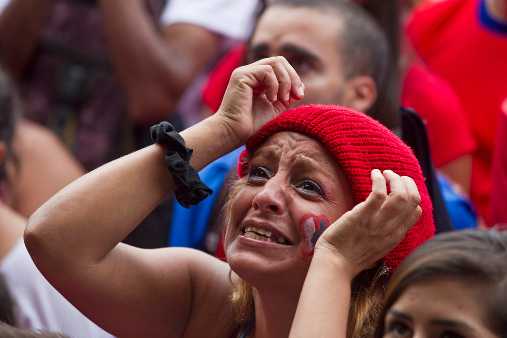 . A Costa Rica soccer fan watches her team\'s World Cup round of 16 match against Greece on TV set up in a public square in San Jose, Costa Rica, Sunday, June 29, 2014. (AP Photo/Esteban Felix)