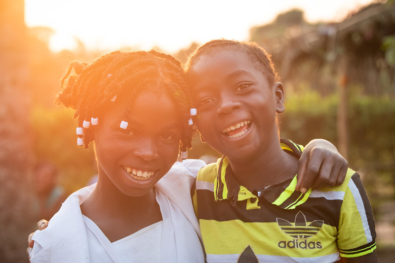 """Kapinga Alphoncine, 13 yr-old girl (in white) with her bet friend, Vicky.  She lives with her grandmother, Kapinga Godelive, 66 and her 3 brothers: 1-Francois Ngondo, 14 2-Mbuyamba Phillip, 9 3-Beya Honore, 6 Kananga, DRC Democratic Republic of Congo.  Play Kapinga and Ngalula Vicky, 12, (just call her Vicky) love to be together. Sometimes fetching water, sometimes doing each other's hair, walking or singing and dancing. This afternoon they sit under a mango tree while Vicky combs and braids Kapinga's hair. They chat like girlfriends do.  Later, outside of Kapinga's house they sing a song in French and dance in a circle.  """"Good morning my friend, good morning. Come and play with me!""""  Inside Kapinga's four-room house the walls are paint splattered. There is little furniture except for two small tables and an old cabinet. On top sits a dusty old television. A peek behind reveals that it has no cord. Kapinga sits on a low, wooden bench against one wall reading an old school exercise book of English lessons. """"Good morning my friends, good morning.""""  Her English is good in spite of a mispronunciation here and there. High up on the wall to the right is a crucifix. It's as battle worn as the rest of the house. Light streams in through the numerous holes in the tin-sheeted roof. In the yard outside, the house is ringed on all sides with gardens of potato and cassava leaves, sorrel and sugarcane among other things.  In one corner of the yard a few visitors gather on homemade chairs under a thatched-roof patio. Across the compound the afternoon sun throws light on the smaller of the two buildings there. In chalk, just below the roof line are the words, """"Il n'ya pas de rose sans epines."""" There is no rose without thorns.  Home Life Her family is living with her grandmother since her dad died. Her mom went off to look for work. She has 3 brothers,1 older and 2 younger. 1-Francois Ngondo, 14 2-Mbuyamba Phillip, 9 3-Beya Honore, 6  She helps her grandmother by sweeping the compou"""