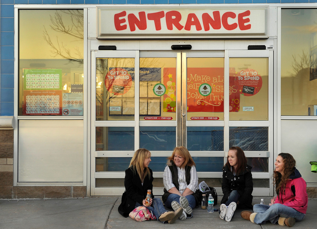 . Desi Maughan, center, was joined by her twin daughters Whitny and Courtney and her daughter-in-law Erica Davis, right, on the sidewalk in front of the Toys R Us store on County Line Road in Arapahoe County Thursday night, November 28, 2013 and waited until the store opened at 5 p.m. Maughan was the first in line and wanted to buy presents for her two grandchildren. Photo By Karl Gehring/The Denver Post