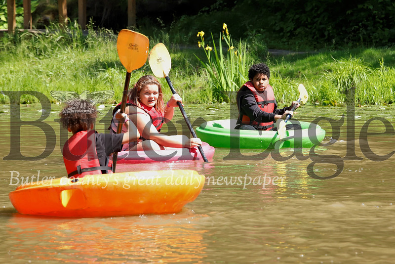Shann Israel (right) of Harmomy, Mykenzee Hawk of Ohio, and  Ivyuan Johnson  of Erie  enjoy a sunny day paddling on the pond at YMCA Camp Kon-O-Kee as part of Allegheny Health Network's burn camp. Seb Foltz/Butler Eagle
