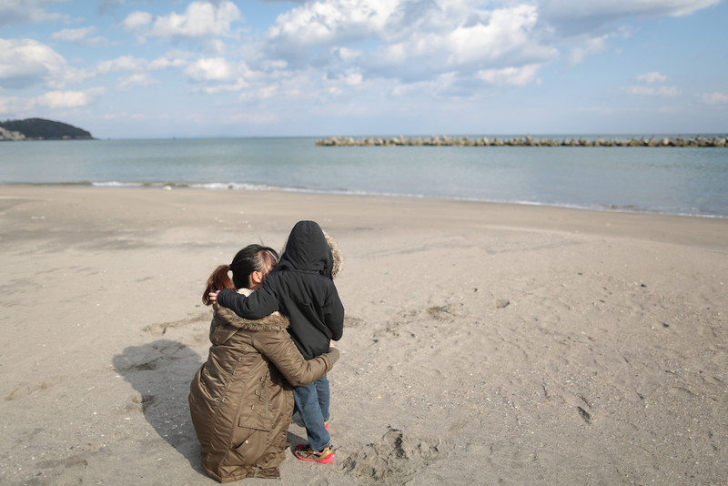 . Yui Goto and her son Kotaro stay close together after observing a moment of silence at 2:46 p.m., the time at which the magnitude 9.0 earthquake struck at Shobuta beach on March 11, 2014 in Shichigahama town, Miyagi Prefecture, Japan. On March 11 Japan commemorates the third anniversary of the magnitude 9.0 earthquake and tsunami that claimed more than 18,000 lives, and subsequent nuclear disaster at the Fukushima Daiichi Nuclear Power Plant.  (Photo by Yuriko Nakao/Getty Images)