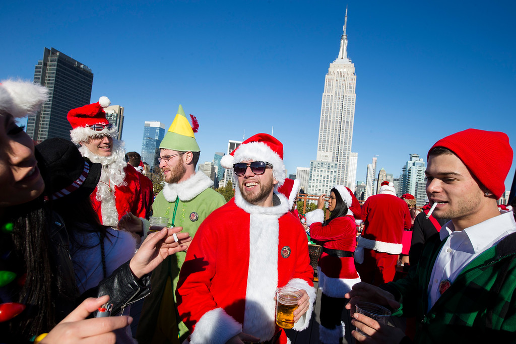 . Revelers dressed in holiday theme costumes participate in SantaCon on Saturday, Dec. 13, 2014, in New York.   SantaCon organizers retained lawyer Norman Siegel  last week as part of an effort to tame the excesses of the daylong party.  Siegel said the government cannot ban SantaCon. But he said the government can reasonably regulate the event. (AP Photo/John Minchillo)