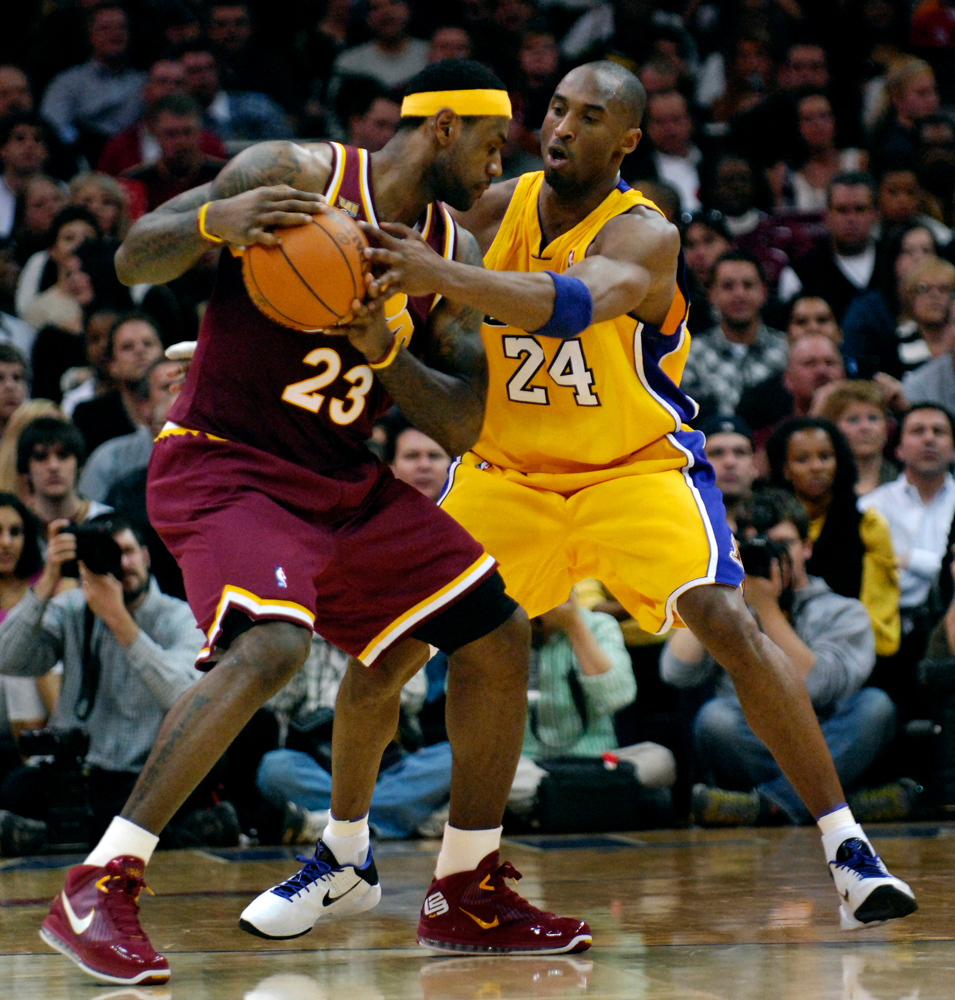 . Jeff Forman/JForman@News-Herald.com Kobe Bryant reaches for the ball as LeBron looks for a shot Thursday at Quicken Loans Arena.