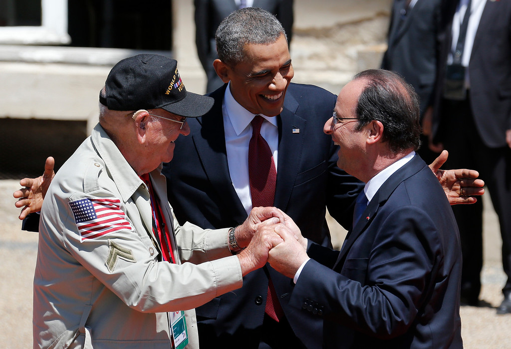 ". U.S. President Barack Obama, center, and French President Francois Hollande, right, smile next to World War II veteran Kenneth ""Rock\"" Merritt as they arrive for the official lunch at Benouville castle, in Normandy, France, Friday, June 6, 2014. (Regis Duvignau, pool)"