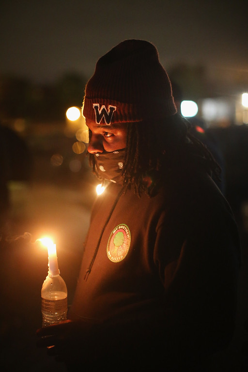 . FERGUSON, MO - OCTOBER 10:  Demonstrators hold a candlelight vigil in memory of Michael Brown and other young minorities killed by gunfire on October 10, 2014 in Ferguson, Missouri. Ferguson has been plagued with protests which have sometimes turned violent since the death of 18-year-old Michael Brown, who was shot and killed by Darren Wilson, a Ferguson police officer, on August 9.  (Photo by Scott Olson/Getty Images)