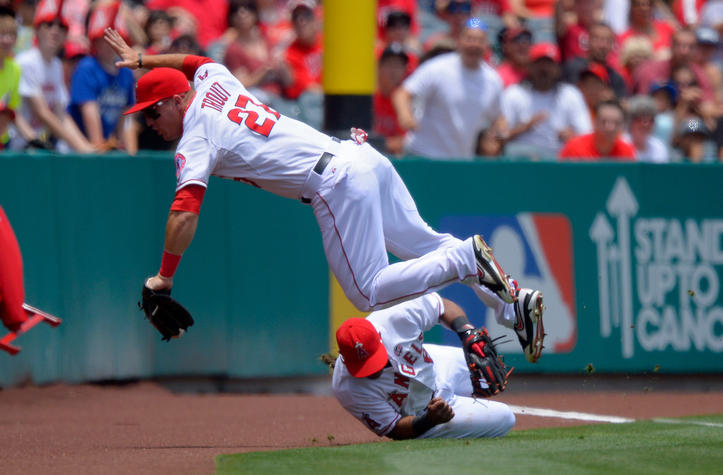 . Los Angeles Angels center fielder Mike Trout, top, trips over third baseman Alberto Callaspo as they try to get a foul ball hit by Pittsburgh Pirates\' Pedro Alvarez during the first inning of their baseball game on Sunday, June 23, 2013, in Anaheim, Calif. Alvarez was safe on the play. (AP Photo/Mark J. Terrill)