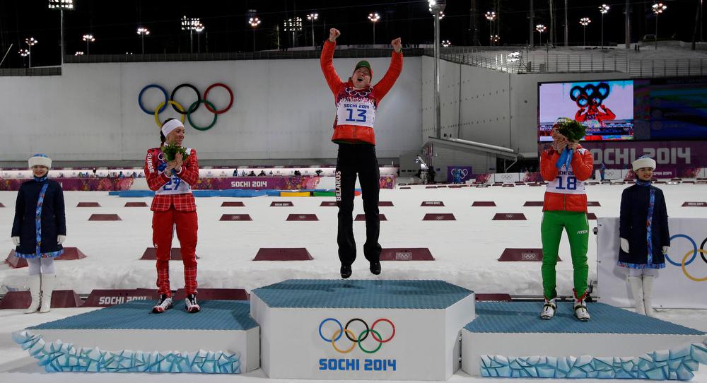 . Silver medalist Switzerland\'s Selina Gasparin, left, gold medalist Belarus\' Darya Domracheva, center, and bronze medalist Belarus\' Nadezhda Skardino attend the flowers ceremony for the women\'s biathlon 15k individual race, at the 2014 Winter Olympics, Friday, Feb. 14, 2014, in Krasnaya Polyana, Russia. (AP Photo/Lee Jin-man)