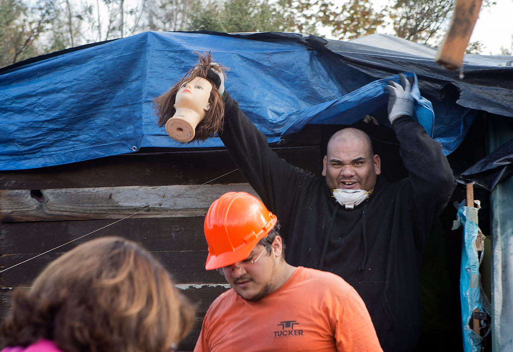 . A worker from Tucker Construction displays a mannequin head found in a campsite in the homeless encampment known as The Jungle in San Jose, Calif., on Thursday, Dec. 4, 2014. (LiPo Ching/Bay Area News Group)