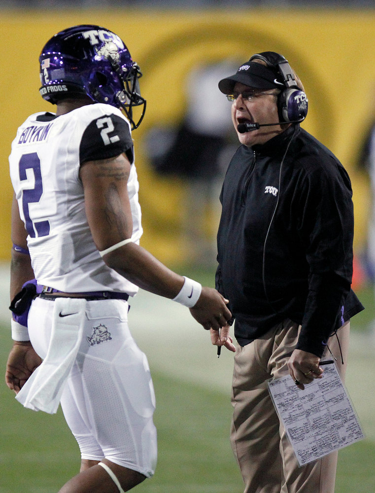 Description of . TCU coach Gary Patterson, right, shouts at quarterback Trevone Boykin, left, as Boykin walks off the field against Michigan State during the first half of the Buffalo Wild Wings Bowl NCAA college football game Saturday, Dec. 29, 2012, in Tempe, Ariz. (AP Photo/Paul Connors)