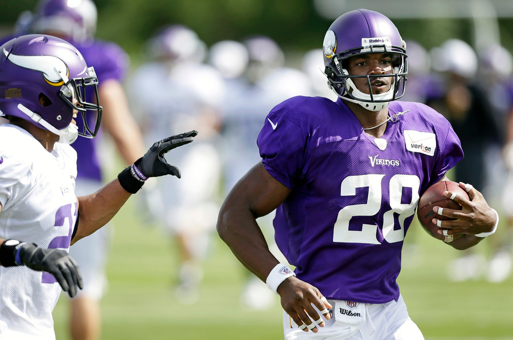 . Vikings running back Adrian Peterson runs a route past cornerback Josh Robinson. (AP Photo/Charlie Neibergall)