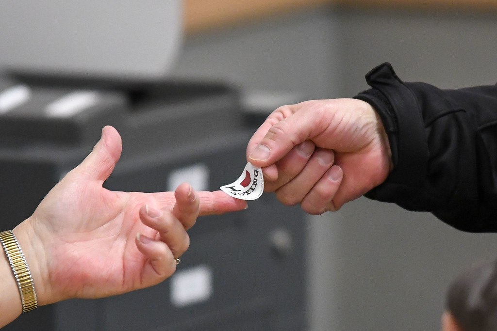 . Eric Bonzar�The Morning Journal<br> A voter gets their sticker from a poll worker at Ritter Public Library, in Vermilion, Nov. 7, 2017.