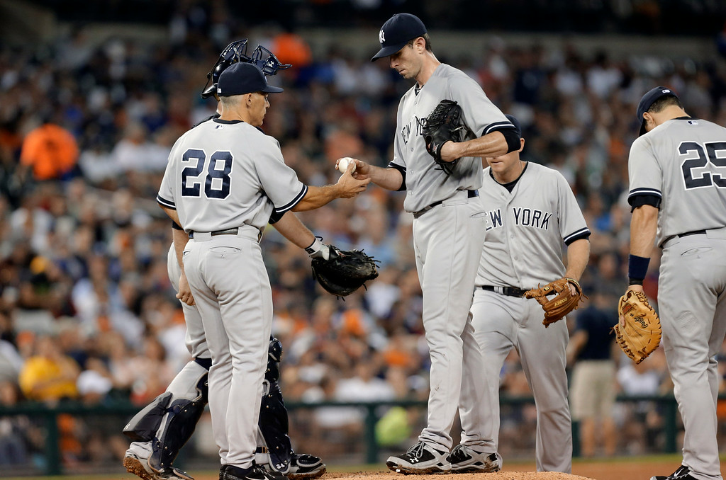 . New York Yankees manager Joe Girardi (28) takes the ball from pitcher Brandon McCarthy in the seventh inning of a baseball game against the Detroit Tigers in Detroit Tuesday, Aug. 26, 2014. (AP Photo/Paul Sancya)