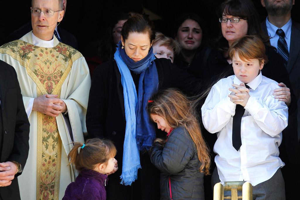 . Mimi O\'Donnell, center, estranged partner of actor Philip Seymour Hoffman, comforts her daughter Tallulah, along with daughter Willa, left, and son Cooper, as Hoffman\'s casket is loaded into a waiting hearse after his funeral Friday, Feb. 7, 2014, in New York. Hoffman, 46, was found dead Sunday of an apparent heroin overdose. (AP Photo/Jason DeCrow)