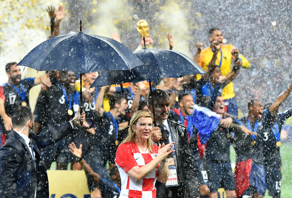 . Croatian President Kolinda Grabar-Kitarovic, right, applauds as French players celebrate after winning 4-2 in the final match between France and Croatia at the 2018 soccer World Cup in the Luzhniki Stadium in Moscow, Russia, Saturday, July 14, 2018. (AP Photo/Martin Meissner)