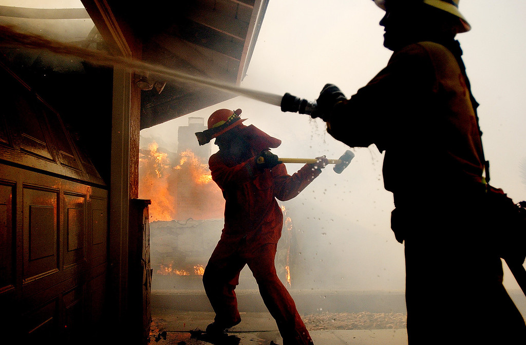 . Ten years ago this month the arson caused Old Fire, fanned by Santa Ana winds burned thousands of acres, destroyed hundreds of homes and caused six deaths. The fire burned homes in San Bernardino, Highland, Cedar Glen, Crestline, Running Springs and Lake Arrowhead and forced the evacuation of thousand of residents.  San Bernardino County Fire Fighter Jacques Plummer, right, sprays water on a home as a inmate fire fighter tries to break down a garage door while fighting the Old Fire in San Bernardino. (Staff file photo/The Sun)