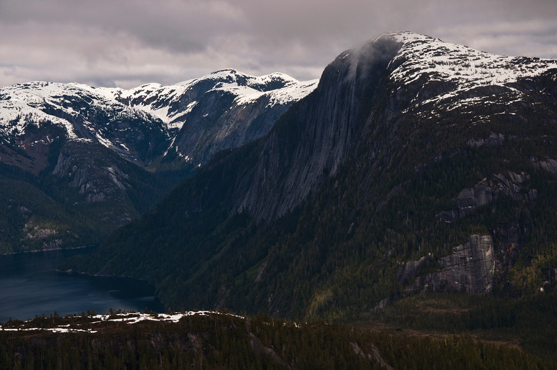 A sharp cliff drops off into a lake in Misty Fjords.