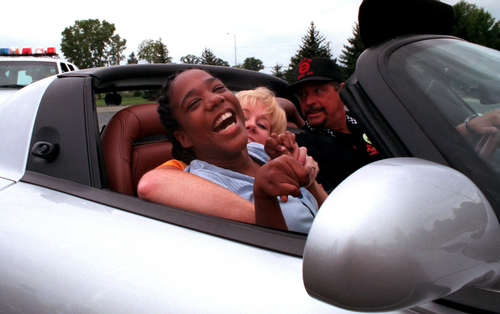 . Siakara Cooper,19, (foreground), sits on her teacher Kathy Wells\' lap as she cruises around the parking lot in a Dodge Viper at the Kennedy Dream Cruise.  The kids from the center were given the opportunity to take rides in three different cars around the parking lot following a 50s and 60s dance at the Kennedy Center.