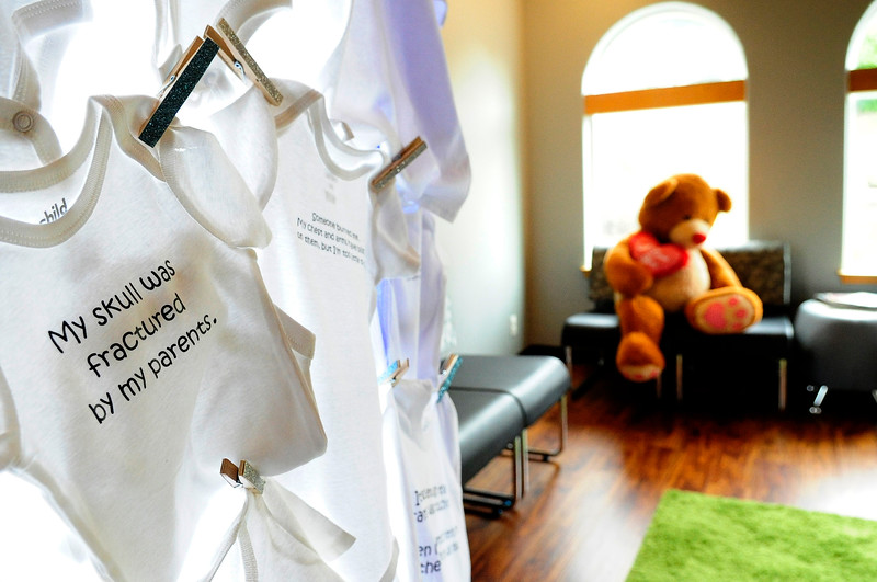 A onesie with a description of a previous child abuse case in Coos County is on display at the Kids' Hope Center on Wednesday. The staff created the display using first-person statements that summarize previous cases on t-shirts or onesies that correspond to the child's age in the case.