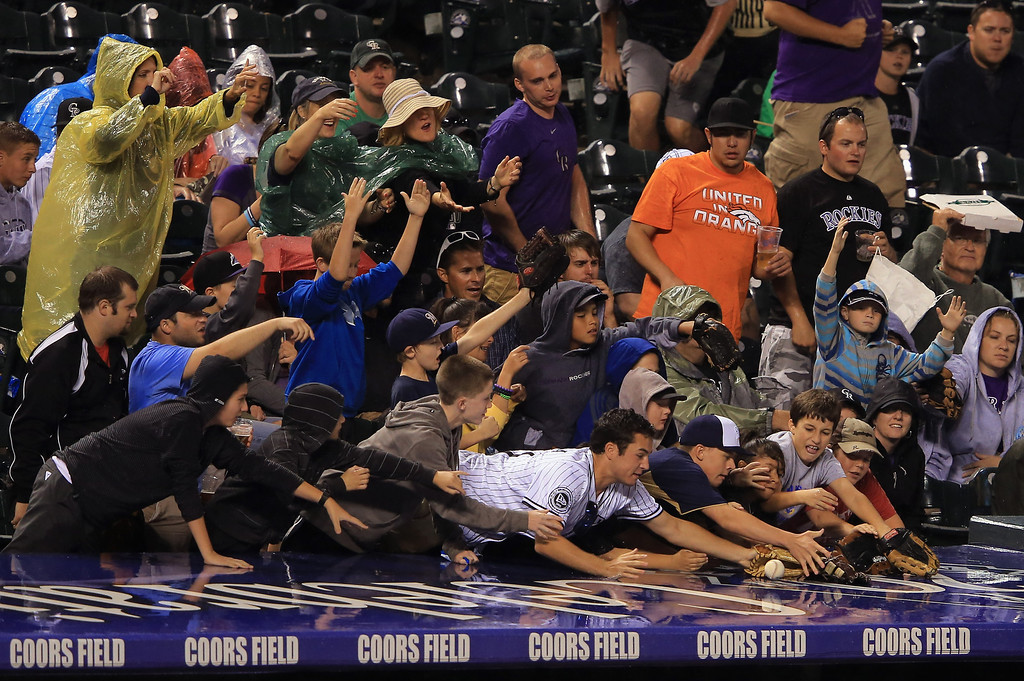 . DENVER, CO - JULY 27:  Fans scramble for a ball tossed on the roof of the Milwaukee Brewers dugout as they face the Colorado Rockies at Coors Field on July 27, 2013 in Denver, Colorado.  (Photo by Doug Pensinger/Getty Images)