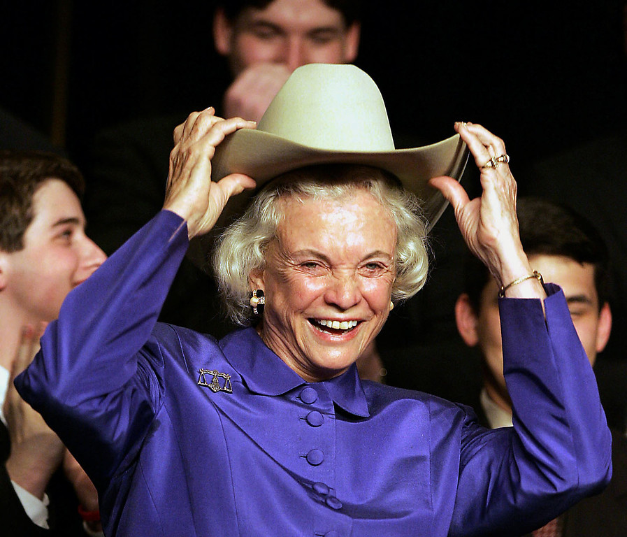 . FILE - In this Thursday, March 10, 2005, file photo, former Supreme Court Justice Sandra Day O\'Connor, an El Paso, Texas, native, dons a cowboy hat given to her during an event at the University of Houston Law Center, in Houston. The Texas legislature is considering making the cowboy hat the official hat of Texas. (AP Photo/Houston Chronicle, James Nielsen, Pool, File)