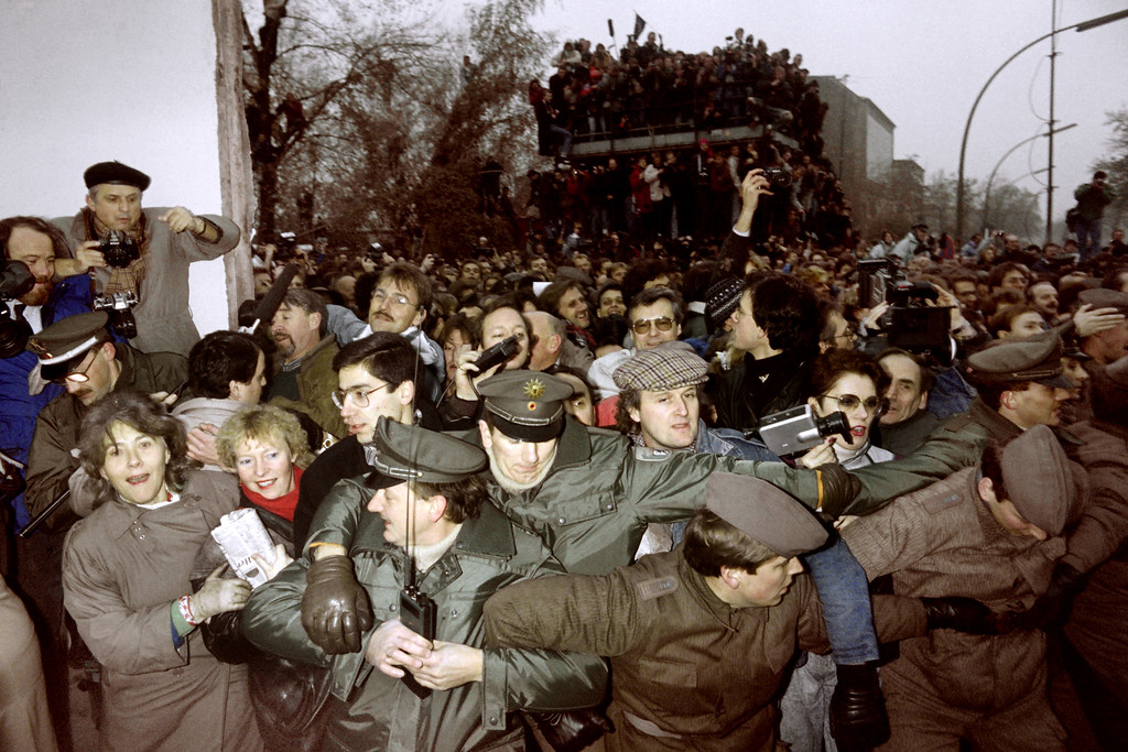 """. East and West German Police contain the crowd of East Berliners flowing through the recent opening made in the Berlin wall at Potsdamer Square, on November 12, 1989. Three days before, Gunter Schabowski, the East Berlin Communist party boss, declared that starting from midnight, East Germans would be free to leave the country, without permission, at any point along the border, including the crossing-points through the Wall in Berlin. The Berlin concrete wall was built by the East German government in August 1961 to seal off East Berlin from the part of the city occupied by the three main Western powers to prevent mass illegal immigration to the West. According to the \""""August 13 Association\"""" which specializes in the history of the Berlin Wall, at least 938 people - 255 in Berlin alone - died, shot by East German border guards, attempting to flee to West Berlin or West Germany.   (Photo credit PATRICK HERTZOG/AFP/Getty Images)"""