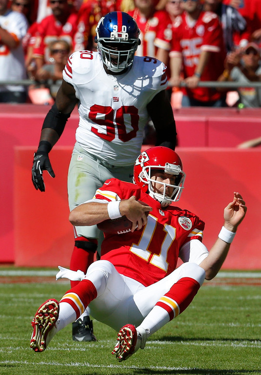 . Kansas City Chiefs quarterback Alex Smith (11) slides down after getting past New York Giants defensive end Jason Pierre-Paul (90) during the first half of an NFL football game at Arrowhead Stadium in Kansas City, Mo., Sunday, Sept. 29, 2013. (AP Photo/Orlin Wagner)