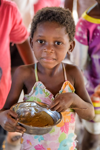 Children enjoy nutritional porridge during a supplemental feeding at the Child Friendly Space that Marie Ngalula, 14, and her siblings attend.  Marie lives with her father, Alexandre Tshimanga, her mother, Ntumba Kalombo Antoinette and her brothers and sisters: 1-Kena Tshimanga, 12 2-Kankonde Moise, 10 3-Munamba Angel, 8 4-Musungayi Andre, 6 5-Mubuyi Tshimanga, 4  Marie lives in a small village outside of Kananga, Democratic Republic of Congo, DRC, called Tubuluku, which means antelopes (plural). Her house is a two-room hut with a thatched roof.  Handful of wooden chairs are the only furniture. She lives here with an extended family of 13.  Home Life Marie is a bright girl but there is a sadness in her eyes. Marie's mother is in the nearby health clinic with a staph infection that has caused a huge abscess on her right side. It has become very serious. As a result, Marie has assumed many of the household duties.  She's forced, at 14, to assume the duties of an adult. Besides cooking for her brothers and sisters, she sweeps up the husks from palm nuts she crushes. She saves the husks to use as kindling for the fire. Marie and her siblings all sleep together in one room, huddled together for warmth and cover by an old and torn mosquito net.  Hunger Marie's family is desperately hungry in the days we visit them. Because her mother is sick and his father spends his days tending to her in the clinic, there is no money for food. Because there isn't any cassava flour and cornmeal to make fufu, a bread-like dish that's a Congolese staple, Marie and her siblings pick potato leaves from the garden. Marie sharpens a knife on a rock and uses it to chop the leaves into small pieces. She holds a bunch tightly in her left hand and runs the knife through them.  Her cousin, also named Marie Ngalula, pulls some wood from a pile and arranges it between three rocks that will hold the pot. She yanks some thatch from the roof and uses it for kindling. Because they also have no oil or sal
