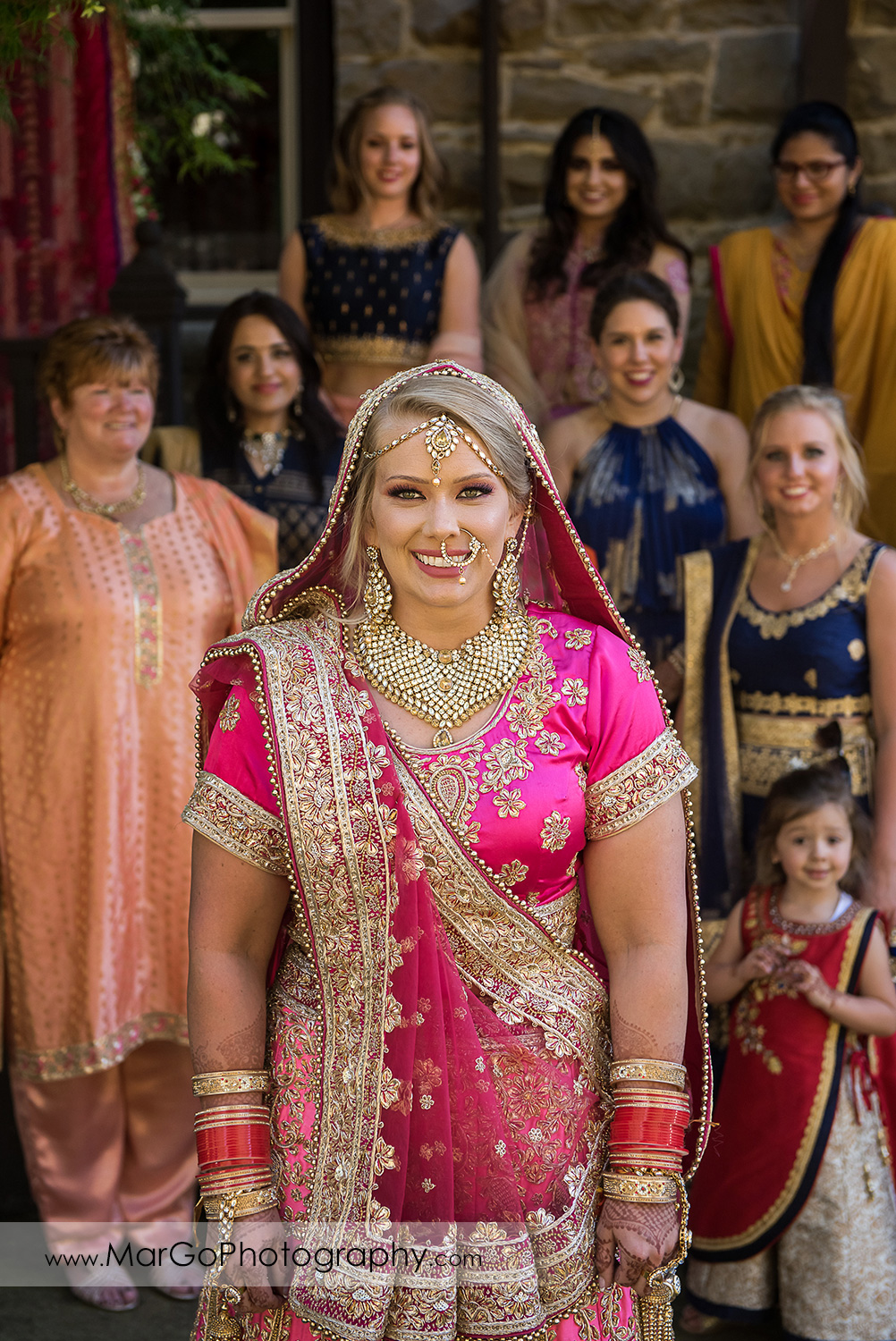 Indian bride in pink saree with bridesmaids in background at Elliston Vineyards in Sunol