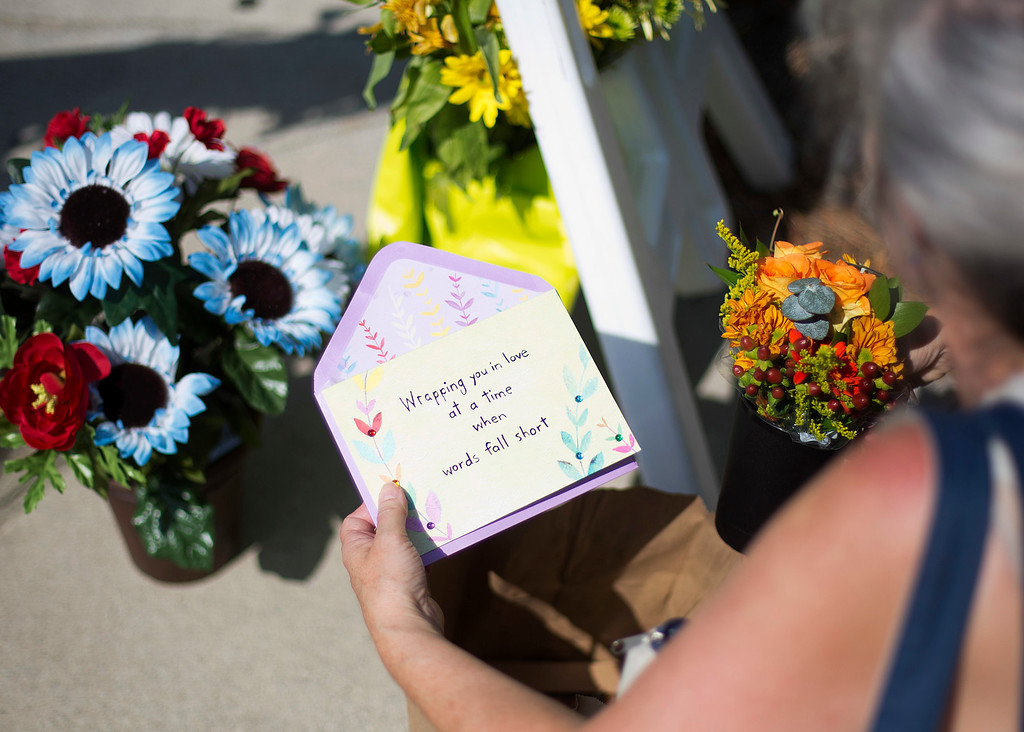 . Sandra Bridges lays a greeting card at a makeshift memorial down the street from where a white man opened fire Wednesday night during a prayer meeting inside a historic black church killing several people in Charleston, S.C., Thursday, June 18, 2015. (AP Photo/David Goldman)