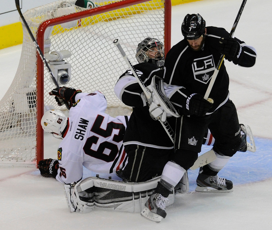 . Blackhawks#65 Andrew Shaw gets tangled up in the goal post after skating past Kings#32 Jonathan Quick and Kings#7 Rob Scuderi in the 2nd period. The Kings played the Chicago Blackhawks in the 3rd game of the Western Conference Finals. Los Angeles, CA 6/4/2013(John McCoy/LA Daily News4