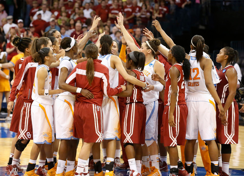Description of . Tennessee and Oklahoma players raise their arms at mid-court following a regional semi-final game in the women's NCAA college basketball tournament in Oklahoma City, Sunday, March 31, 2013. Tennessee won 74-59. (AP Photo/Sue Ogrocki)