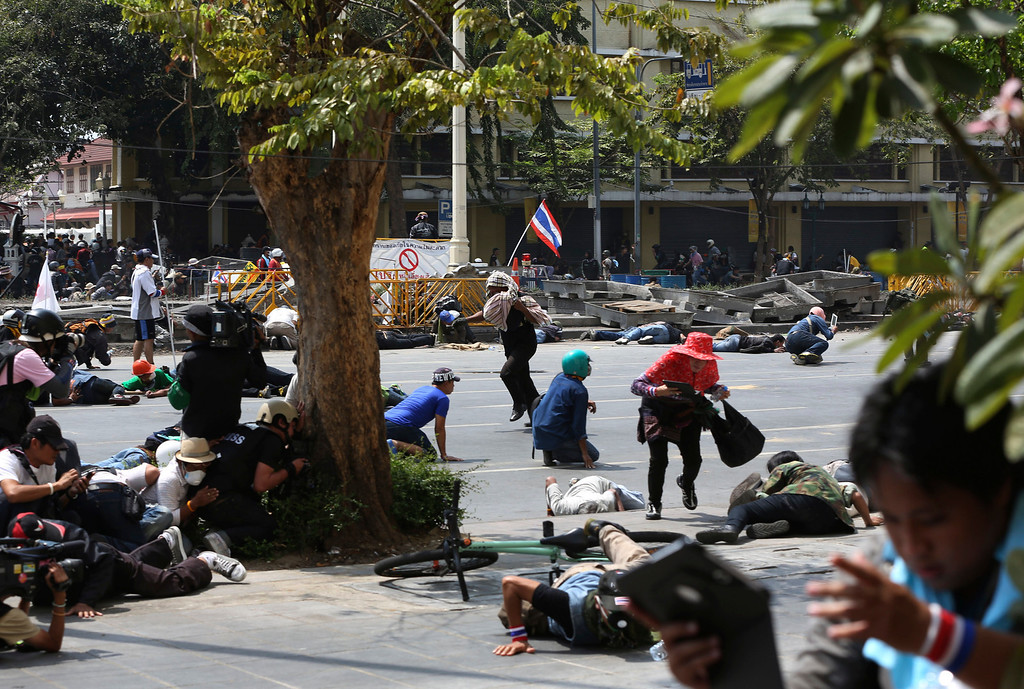 . Protesters and reporters run for cover from police gunfire during a clash between policemen and anti-government protesters Tuesday, Feb. 18, 2014 in Bangkok, Thailand.  (AP Photo/Apichart Weerawong)