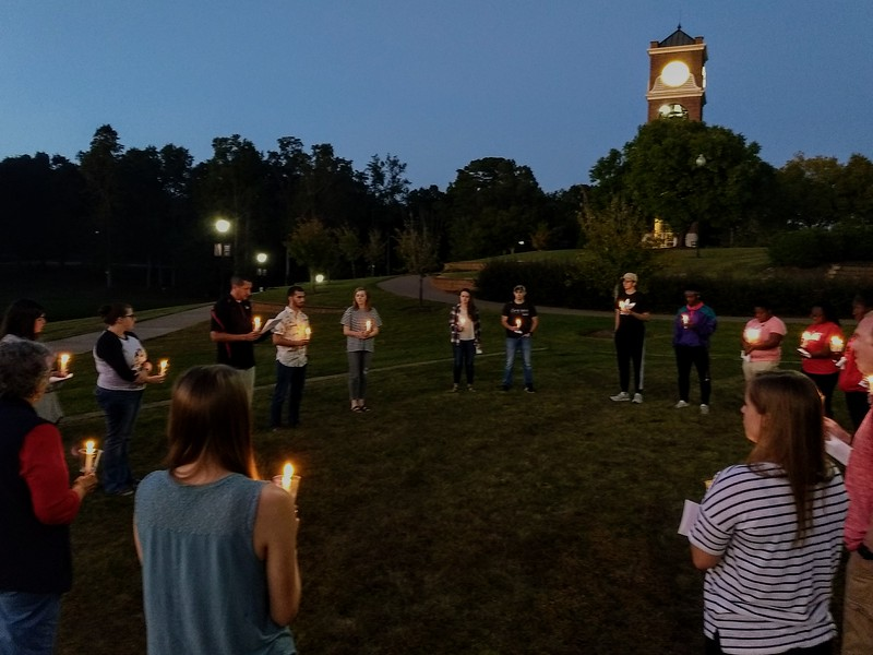 Students gather beside Lake Hollifield for a candle lighting service in honor of Tina Frost, alumni of GWU
