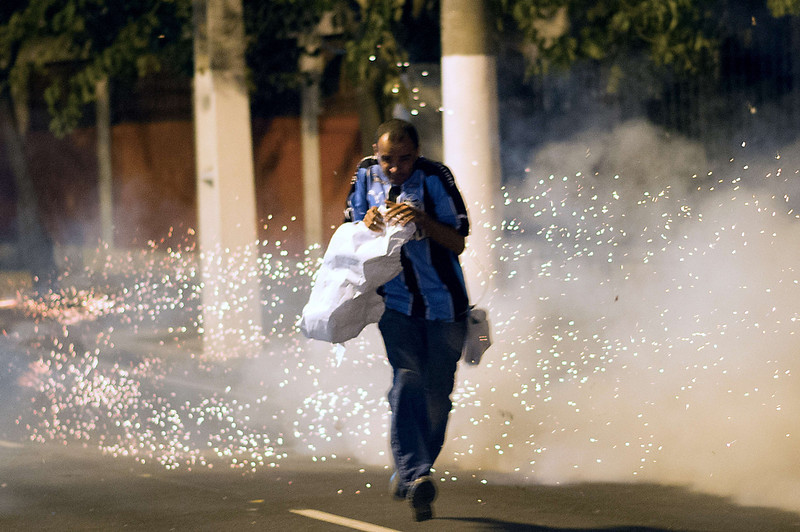. A demonstrator runs from tear gas gunshots fired by military police from the special unit Choque late on June 19, 2013 during clashes in the center of Niteroi, 10 kms from Rio de Janeiro. Protesters battled police late on June 19, even after Brazil\'s two biggest cities rolled back the transit fare hikes that triggered two weeks of nationwide protests.  The fare rollback in Sao Paulo and Rio de Janeiro marked a major victory for the protests, which are the biggest Brazil has seen in two decades.   CHRISTOPHE SIMON/AFP/Getty Images