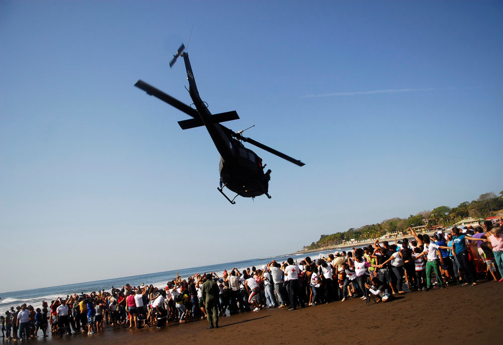 Description of . A helicopter hovers over the beach after assisting participants of the annual Paso del Hombre endurance challenge at La Libertad port in El Salvador February 24, 2013. About 370 male and female lifeguard volunteers swam for four to five hours continuously during the 49th edition of the event organized by the Salvadorian Red Cross in collaboration with the Navy, Coast Guard, Air Force and Civil National Police, local media reported. Picture taken February 24, 2013.  REUTERS/Ulises Rodriguez