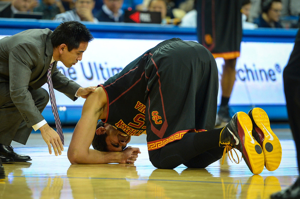 . USC�s Omar Oraby grimaces after an ankle injury during game action at Pauley Pavilion Sunday, December 5, 2014. UCLA  defeated USC 107-73.  Photo by David Crane/Los Angeles Daily News.