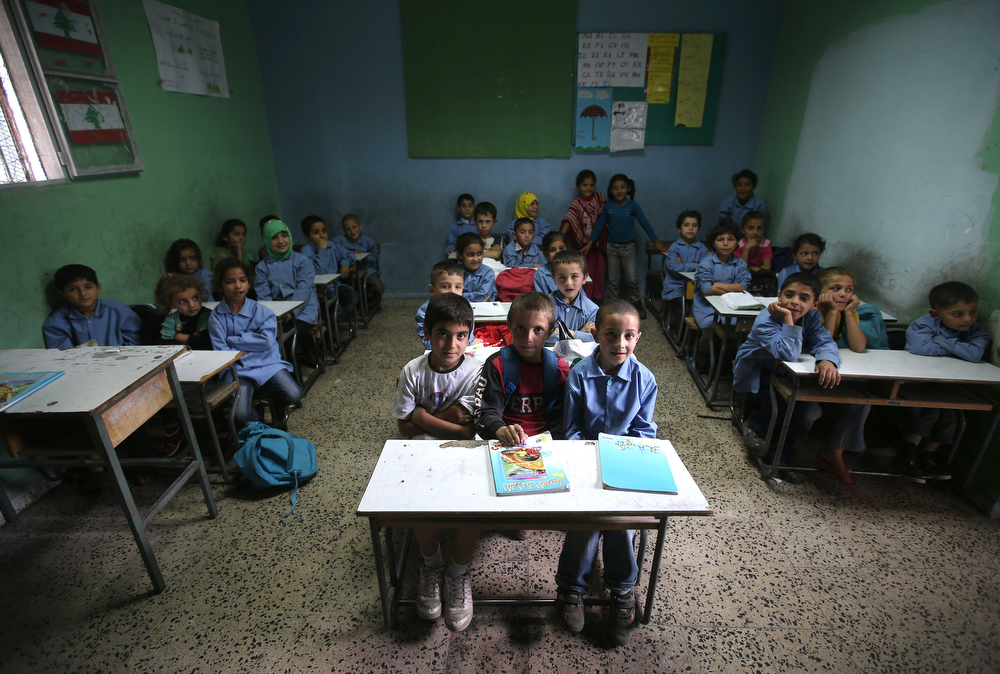. In this picture taken on Thursday, May 29, 2014, Syrian refugee students attend an Arabic lesson as they sit in a classroom at a Lebanese public school where only Syrian students attend classes in the afternoon, in Kaitaa village in north Lebanon. (AP Photo/Hussein Malla)