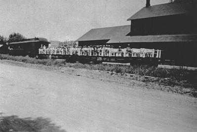 SY - Railroad flatcar carrying folks on an excursion.  Undated.