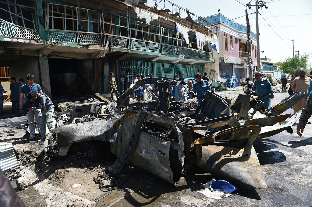 . Afghan policemen walk around a destroyed US military vehicle  at the site of a suicide attack in Kabul on May 16, 2013.   AFP PHOTO/ Massoud HOSSAINI/AFP/Getty Images