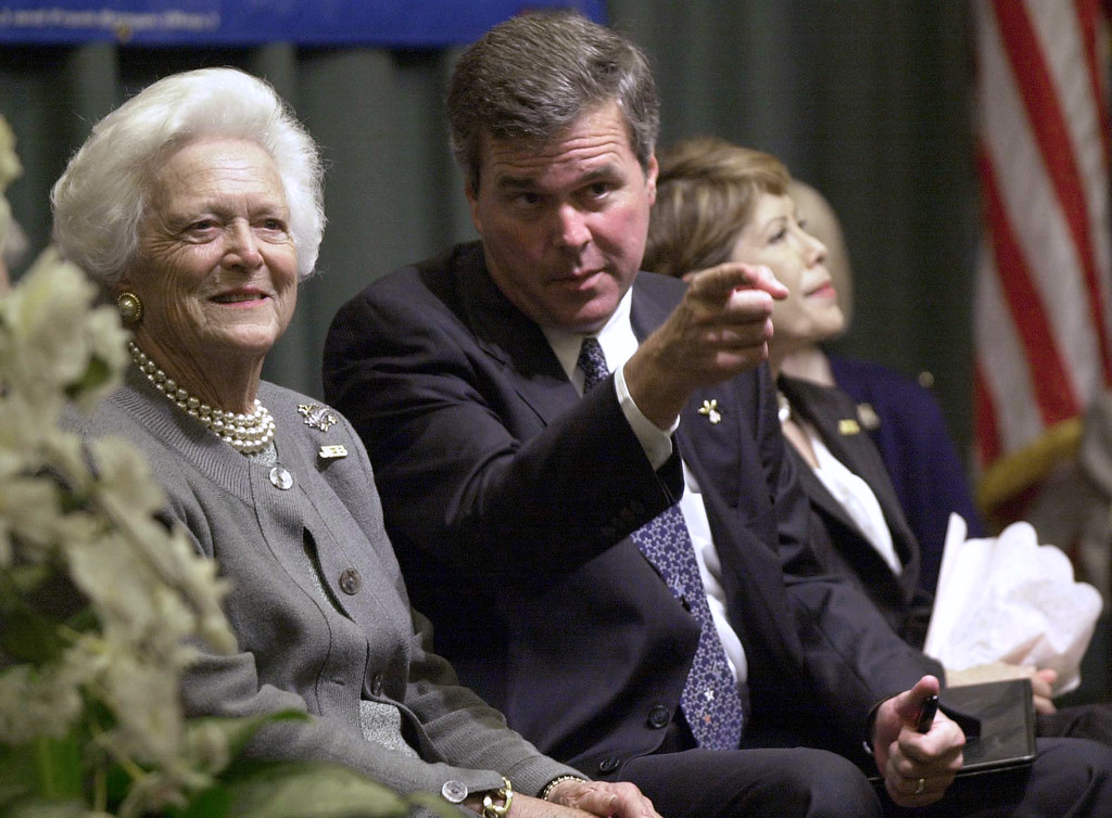 . Florida Gov. Jeb Bush, center, points out residents of a retirement community to his mother, former first lady Barbara Bush, during a campaign stop Monday, Oct. 21, 2002, in Cape Coral, Fla. Florida first lady Columba Bush sits at right. (AP Photo/Chris O\'Meara)