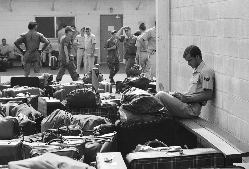 . Surrounded by luggage of other departing GIs, U.S. Air Force airman reads paperback novel as he waits to begin processing at Camp Alpha on Saigon\'s Tan Son Nhut airbase in Saigon as troop withdrawals resume after 10 day-delay, March 27, 1973. More than 900 will leave with all U.S. troops out by Thursday. (AP photo/Charles Harrity)